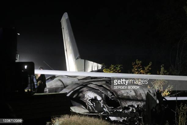 Resquers and experts work on the place of the Antonov-26 transport aircraft crash at Chuhuiv military air base around 30 kilometers southeast of...
