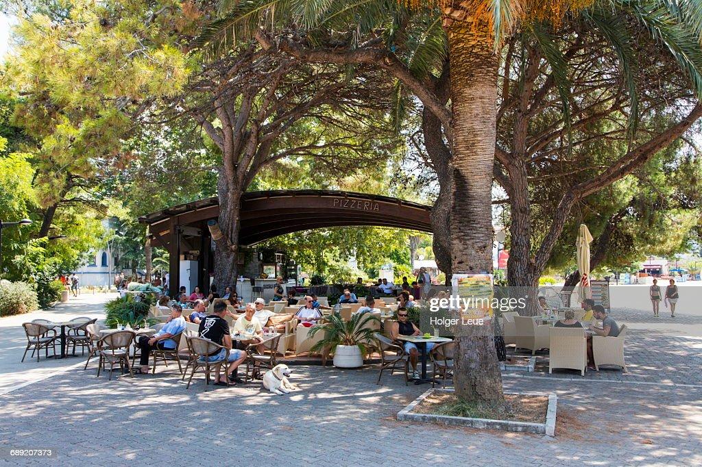 Restaurant and cafe patrons enjoy tree shade : Stock Photo