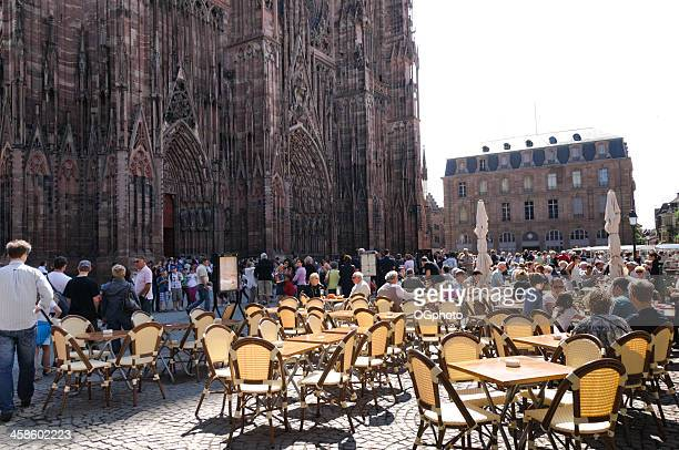 restaurant and crowds in front of strasbourg cathedral - ogphoto stock photos and pictures