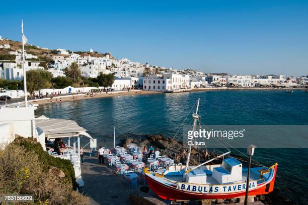 Restaurant by sea, Mykonos Town in background, Cyclades, Greece
