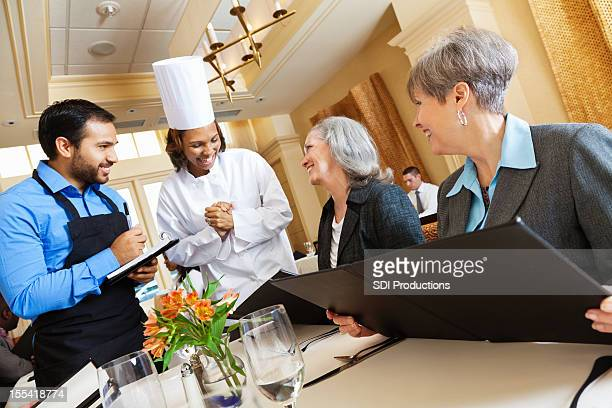 Restaurant chef and waiter helping customers with menu food questions