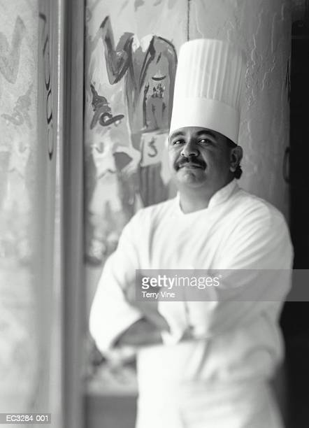 Restaurant chef standing by decorative wall (B&W)