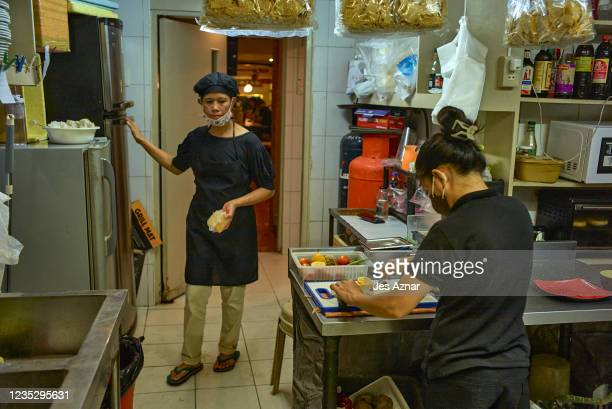 Restaurant crew members prepare food inside the kitchen on September 16, 2021 in Manila, Philippines. The Philippines capital is yet again placed...