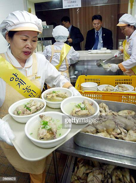 A restaurant employee carries chicken broth with ginseng during an event to boost consumption of chickens at Samsung mutual aid hall refectory in...
