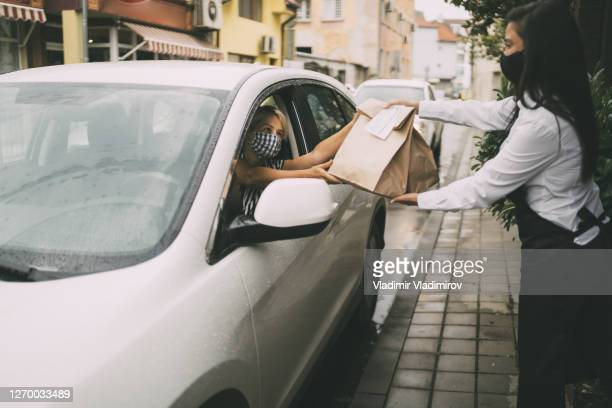 restaurant employee delivers packed food to a female driver. - curbside pickup stock pictures, royalty-free photos & images