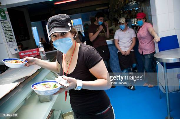 A restaurant employee wearing a protective mask carries plates of food at an eatery in the Condesa neighborhood on May 6 2009 in Mexico City Mexico...