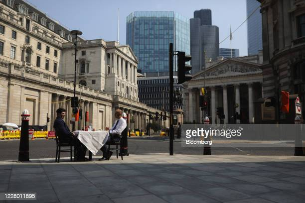 Restaurant employees sit at a dining table while demonstrating outdoor dining seating plans on a pavement outside restaurant 1 Lombard Street, near...