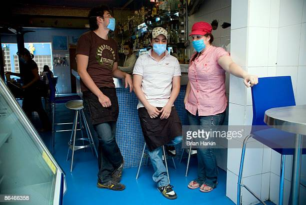 Restaurant employees wearing protective masks wait for customers at an eatery in the Condesa neighborhood on May 6 2009 in Mexico City Mexico The...