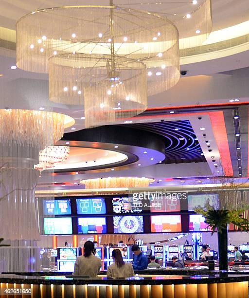 Restaurant employees work next to the casino of the newlyopened City of Dreams megacasino chain in Manila on February 2 2015 Six gleaming golden...