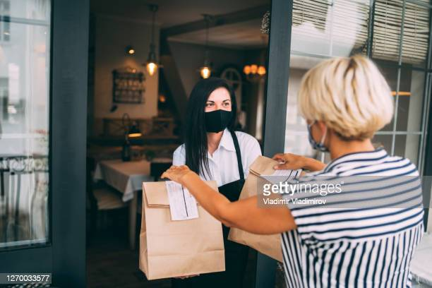 restaurant employer giving packed food away to a customer. reopening after covid-19 quarantine concepts. - take out food stock pictures, royalty-free photos & images