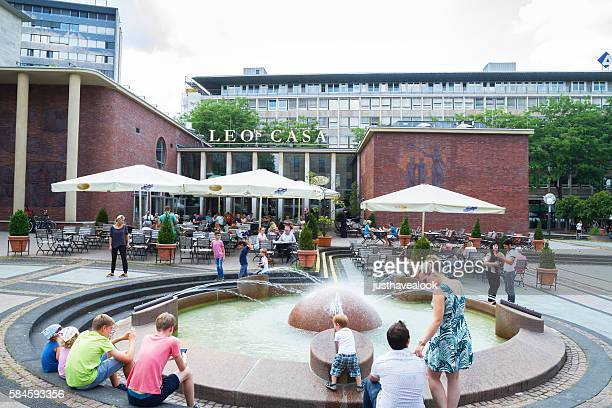 Restaurant, fountain and people on square Kennedy Platz