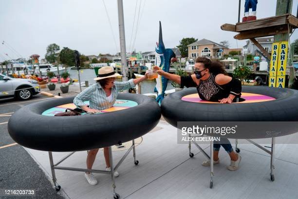 Restaurant guests try out social distancing devices made of rubber tubing as Fish Tails bar and grill opens for in person dining during the...