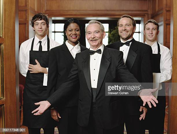 Restaurant host wearing tuxedo, standing in front of staff, portrait