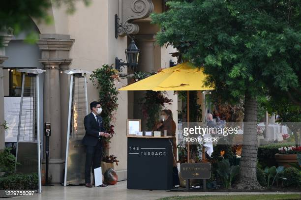 Restaurant hostess wearing a mask and face shields waits for customers at lunch time at a restaurant in Beverly Hills, California, November 23, 2020....