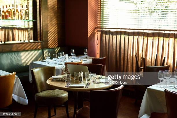 restaurant interior with laptop on table - table stock pictures, royalty-free photos & images