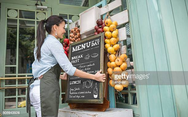restaurant manager hanging the menu at the entrance - menu stock pictures, royalty-free photos & images
