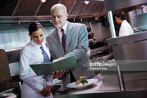 Restaurant manager reviewing menu with waitress in commercial kitchen