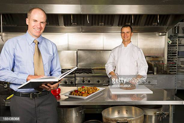 A restaurant manager stood in the kitchen with the chef