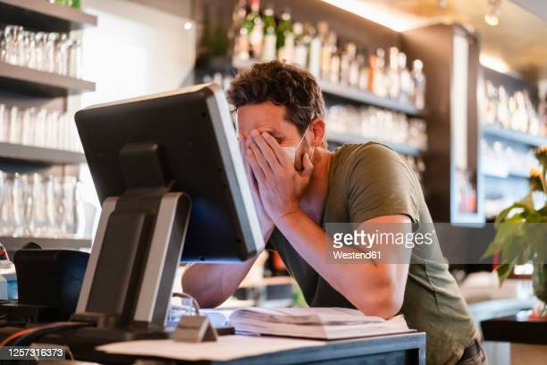 restaurant manager with hands in face during corona crisis - banqueroute photos et images de collection