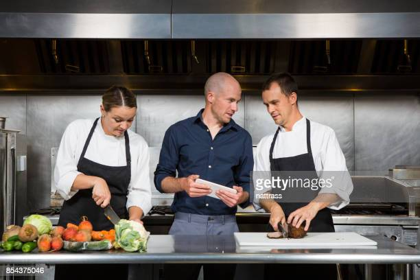 restaurant manager works with his professional chef's - restaurant kitchen stock photos and pictures