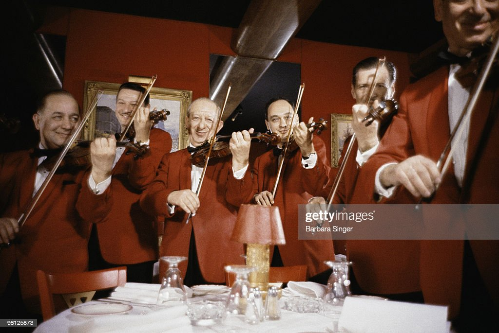 Restaurant musicians playing violins : Stock Photo