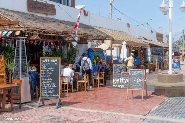 restaurant on the pavement in pisco, peru - pisco peru stock photos and pictures