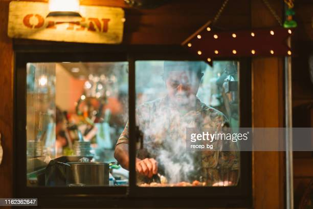 restaurant owner cooking for customers - tokyo japan stock pictures, royalty-free photos & images
