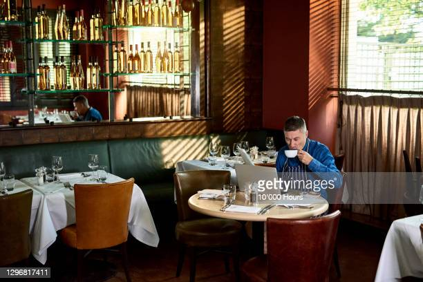 restaurant owner drinking coffee and working in empty restaurant - small business stock pictures, royalty-free photos & images