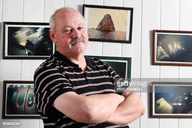 Restaurant owner Frenchman JeanYves Letard poses in front of photos showing the shipwreck of Liberian oil tanker Amoco Cadiz at his restaurant Beg Ar...