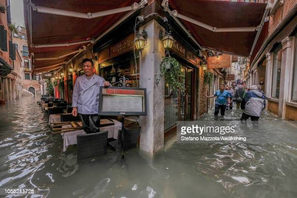 A restaurant owner looks at the flood waters on October 29 2018 in Venice Italy Due to the exceptional level of the acqua alta or High Tide that...