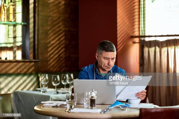 restaurant owner reading documents during pandemic - finance and economy stock pictures, royalty-free photos & images