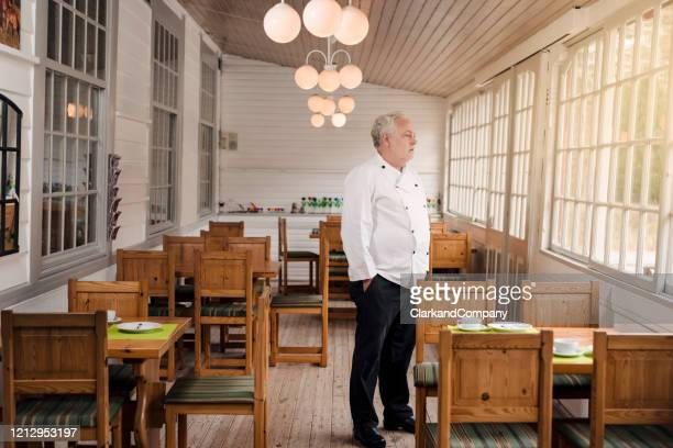 restaurant owner standing in his empty restaurant. - restaurant stock pictures, royalty-free photos & images