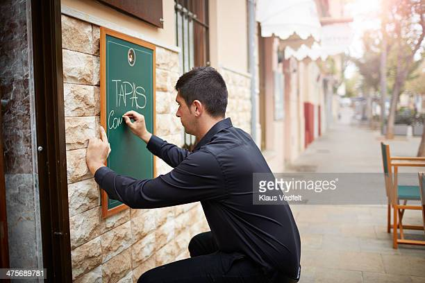 restaurant owner writing tapas dishes on sign - klaus vedfelt mallorca stock pictures, royalty-free photos & images