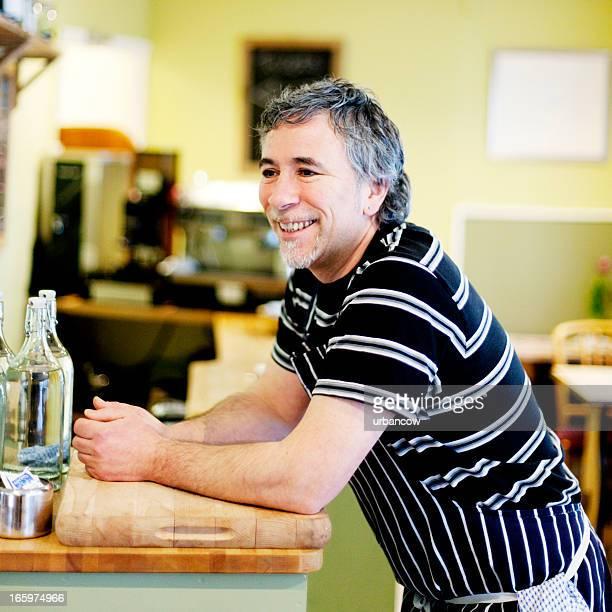 Restaurant proprietor, smiling
