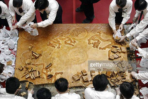 Restaurant staff help cut and bag pieces from a giant mooncake in Beijing 28 September 2004 The traditional midautumn or mooncake festival is...