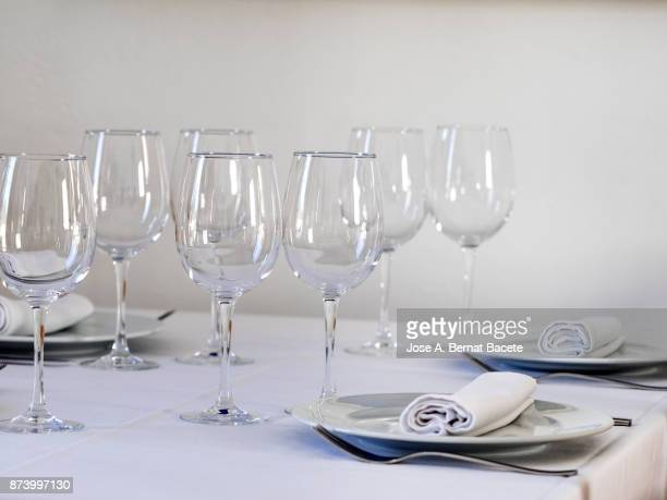 Restaurant table prepared with white tablecloth, napkins, cutlery and wine glasses, with wooden chairs on a white background
