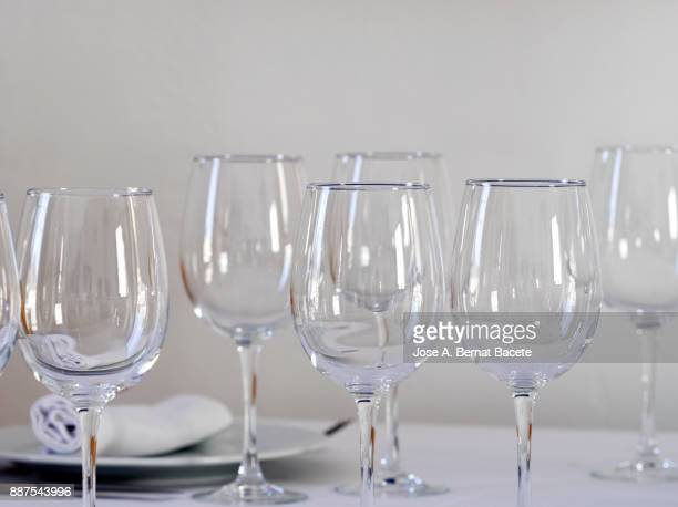 restaurant table prepared with white tablecloth, napkins, cutlery and wine glasses, with wooden chairs on a white background - cleaning after party bildbanksfoton och bilder