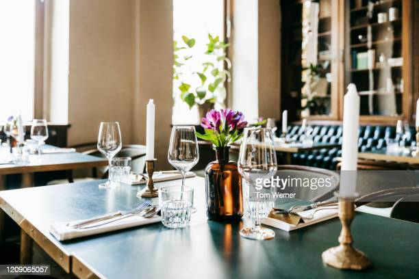 a restaurant table set with wine glasses and candle - restaurant stock-fotos und bilder