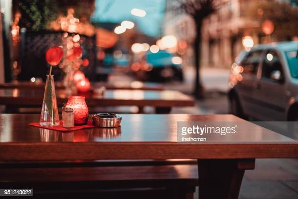 restaurant table with tulip, candle and ashtray with blurried street lights - car decoration stock pictures, royalty-free photos & images