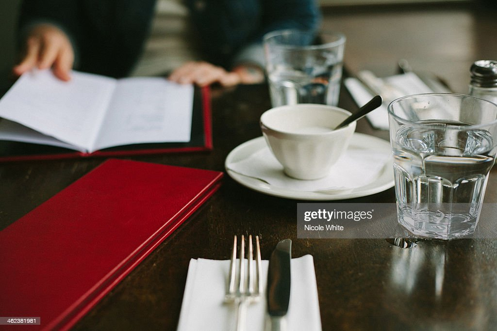 A restaurant table with woman reading a menu : Stock Photo