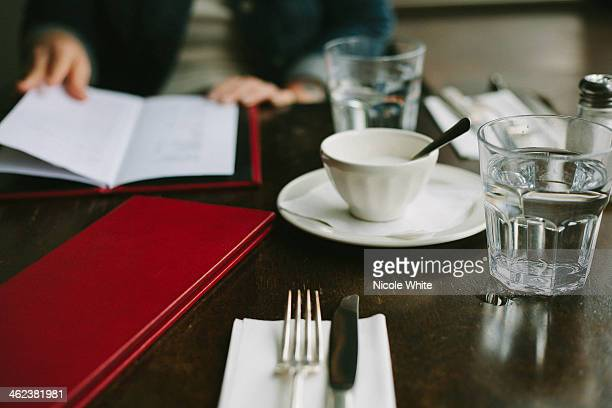 A restaurant table with woman reading a menu