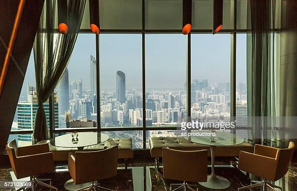 Restaurant tables overlooking Abu Dhabi cityscape, Abu Dhabi Emirate, United Arab Emirates