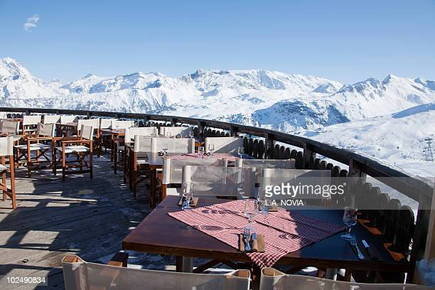 restaurant terrace surrounded by snow covered mountains - courchevel photos et images de collection