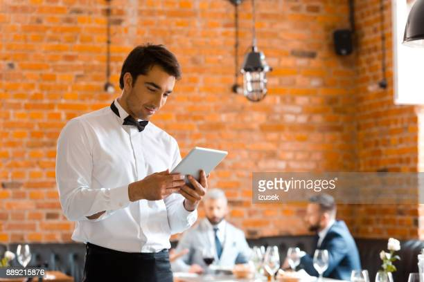 restaurant waiter using digital tablet - izusek stock pictures, royalty-free photos & images