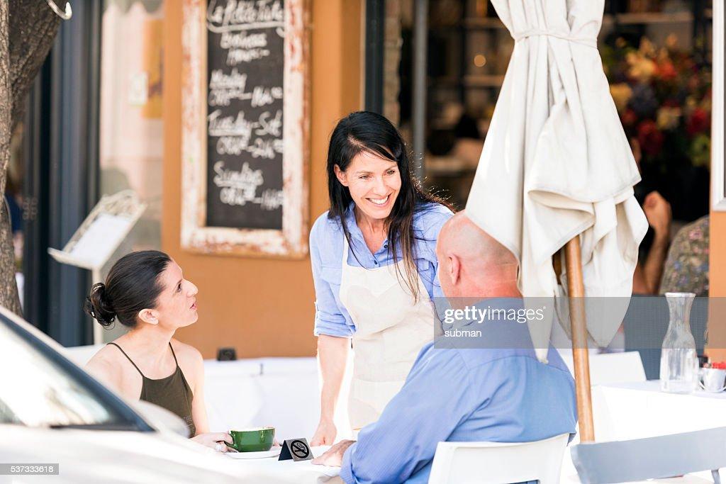 Restaurant Waitress Talking To Her Customers Stock Photo