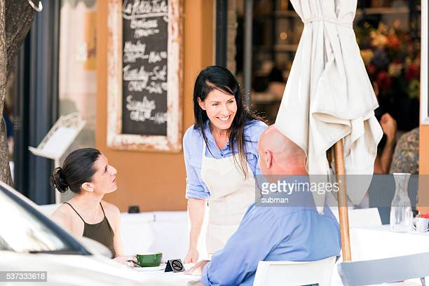 Camarera de restaurante  hablando con sus clientes.