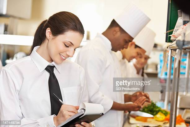 restaurant waitress writing on order book in a commercial kitchen - hair back stock pictures, royalty-free photos & images