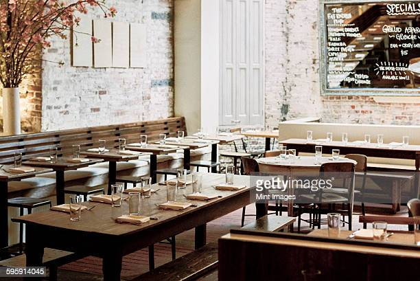 a restaurant with long narrow tables and chairs laid for a meal. a large chalk menu board. - empty restaurant stock pictures, royalty-free photos & images