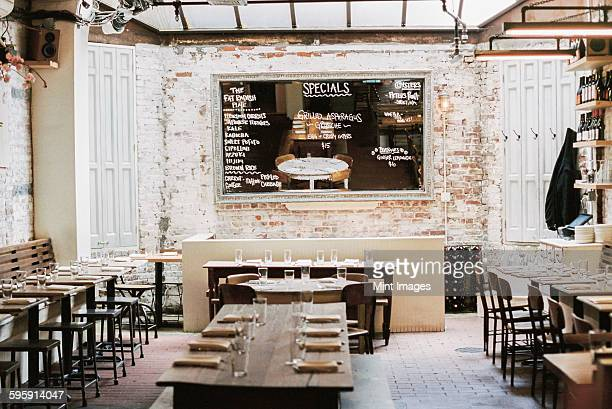 A restaurant with long narrow tables and chairs laid for a meal. A large chalk menu board.