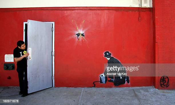 Restaurant worker appears to look on in surprise as a businessman explodes a rat in this Banksy-style stencil graffiti by British street artist Nick...